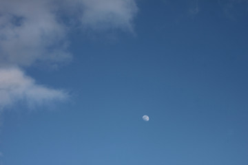Blue sky with white clouds and white moon