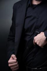 Man in black suit with gun in hands.