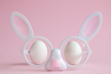 Rabbit eyeglasses and eggs abstract on rose.