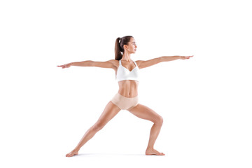 Attractive young woman doing yoga exercise Virabhadrasana, isolated on white background.