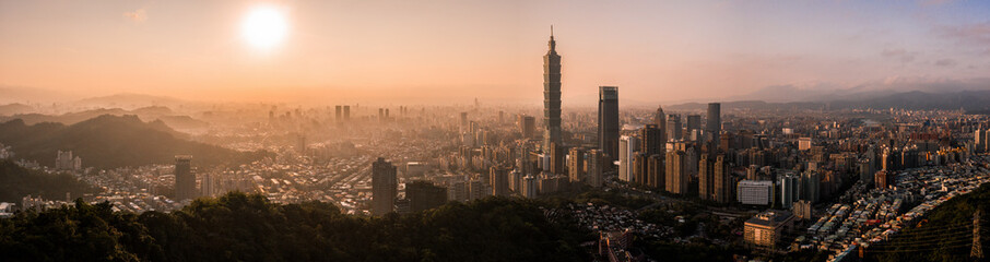 Aerial drone panorama photo - Sunset over the city of Taipei, Taiwan. Taipei 101 skyscraper featured.