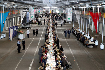Participants sitting at a 401.22 meters table attend a lunch at the fruits and vegetables pavilion, near Paris