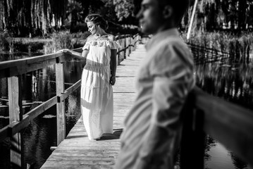 Attractive young couple standing on the bridge over the lake in the countryside. Black and white photo