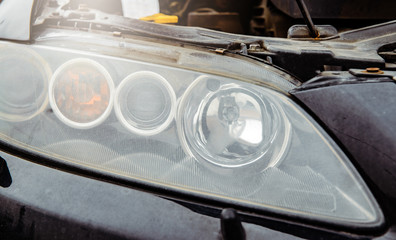 Car headlight with an open car hood. The concept of changing the bulb in the car, no lighting. Problems with the car. Fluid replacement in the car.