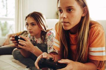Girls playing video games at home