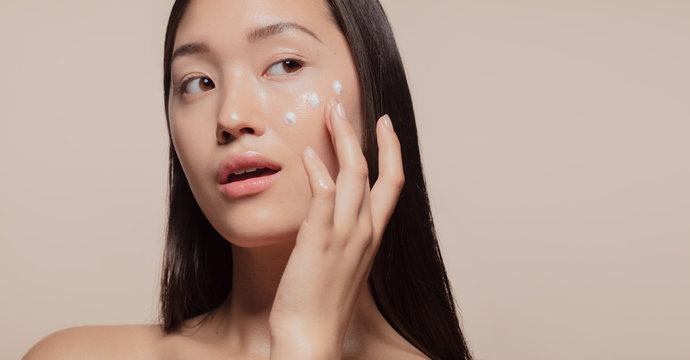 Applying moisturizer to her face