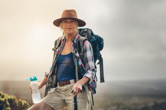 Woman hiker drinking water during her trek
