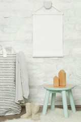 Nicely decorated kids room in pastel colors, wooden toys, furniture and blank white poster on the wall