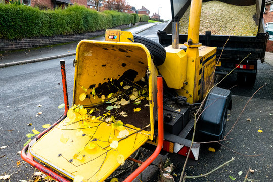 A yellow commercial engine powered drum woodchipper with hopper and wood chipper towed by a tipper truck