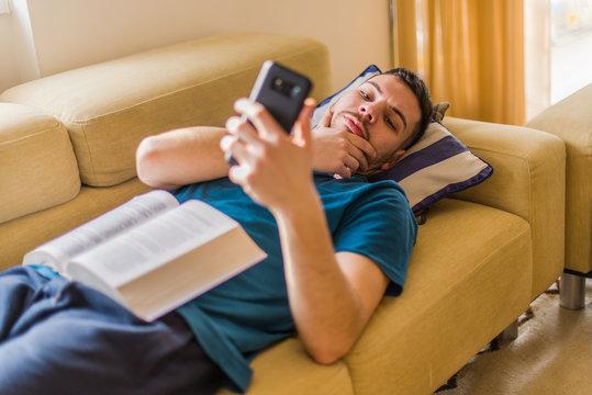 Man looking at his phone, procrastinating, avoiding obligations