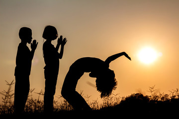 Silhouette group children playing on meadow at sunset time.