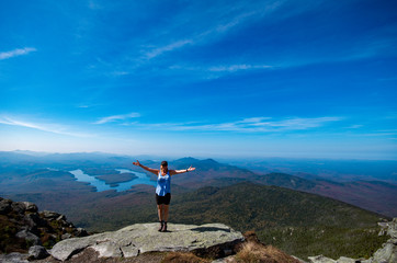 Female hiker standing on the edge of a cliff with her arms out at the summit of Whiteface Mountain