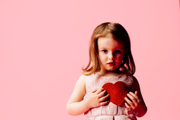 Portrait of a little toddler girl on pink