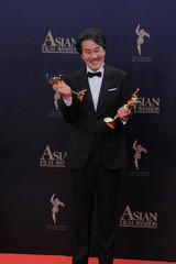 Japanese actor Koji poses with his trophy after winning the best actor award at the 13th Asian Film Awards in Hong Kong