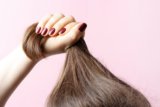 Female hands with red manicure holding hair, pink background, hair care concept