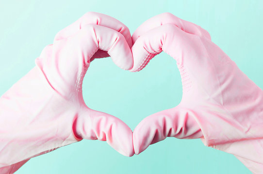 Hands in pink rubber gloves in the shape of a heart on a blue background