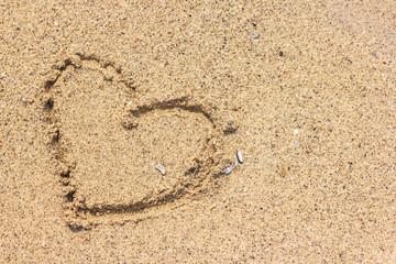 Heart shape drawn on sand at the beach