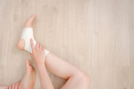 Closeup People of a Foot with White Gauze Elastic Bandage. Hands on Injured Legs and Feet on Pain Area. Asian Young Woman Ankle Injury Runner Sitting on a Wooden Floor Background from Rupture or Tear.