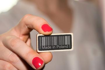 Eine Frau und ein Schild mit einem Barcode und Slogan Made in Poland