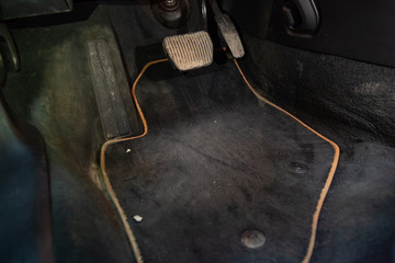 Dirty car floor mats of black carpet with gas pedals and brakes in the workshop for the detailing vehicle before dry cleaning