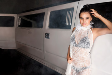 Girl in a transparent dress standing next to a vehicle