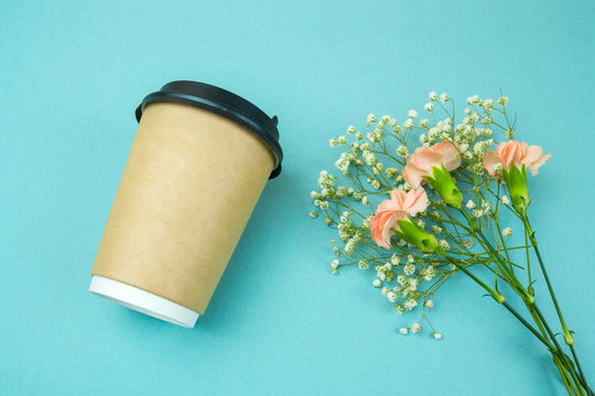 top view paper coffee to go cup  and flwers  on blue  background