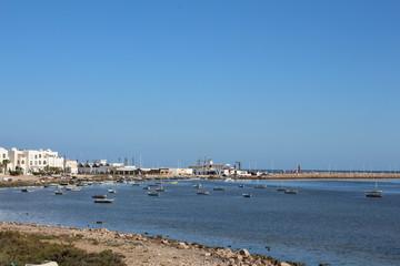 Tunisia, Djerba - 06.08.2017: Seascape. View of the fishing boats that stand near the shore. Stranded, beautiful blue sea, coastline.