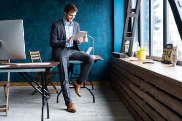 Handsome elegant businessman working on a tablet.