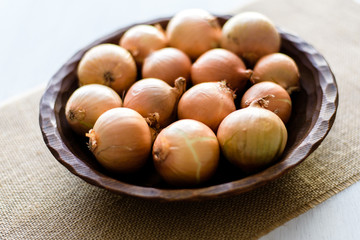 Raw organic onions on rustic wooden bowl. Table background