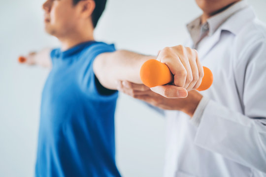 Physiotherapist man giving exercise with dumbbell treatment About Arm and Shoulder of athlete male patient Physical therapy concept