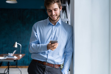 handsome young bearded business man in office using mobile phone indoors.