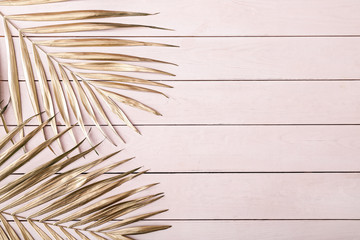 Wall Mural - Painted golden tropical leaves on wooden background