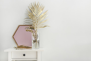 Golden tropical leaves and mirror on table near white wall Fototapete