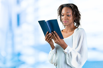 Close-up portrait of a young african woman with a book
