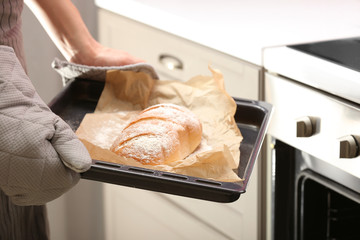 Taking of baking tray with homemade bread out of oven
