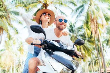 Happy smiling couple travelers riding motorbike during their tropical vacation under palm trees