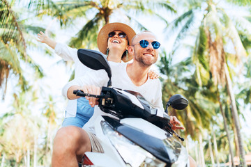 Happy couple going by motorbike under palm trees during their island vacation