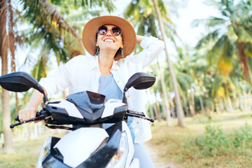 Happy smiling traveller woman riding motorbike under palm trees