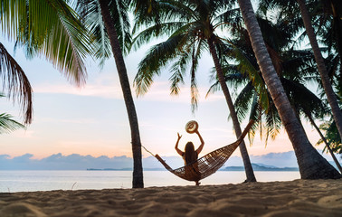 Young woman meeting sunrise sitting in hammock on the sand beach under the palm trees