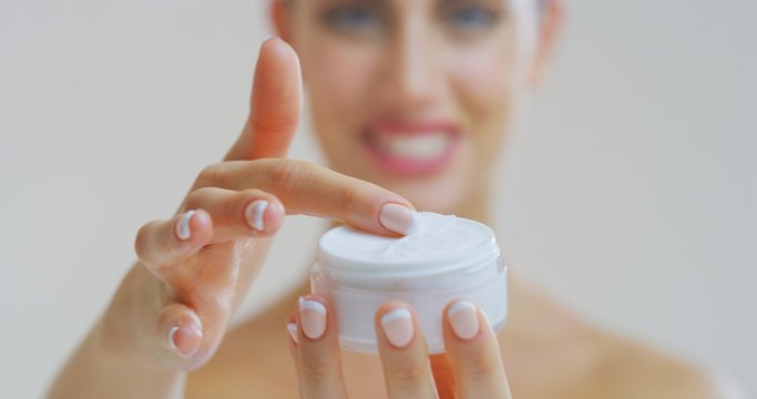 Portrait of woman with beautiful face with perfect skin just cleaned from impurities smiling and showing in camera transparent jar with day or night cream.