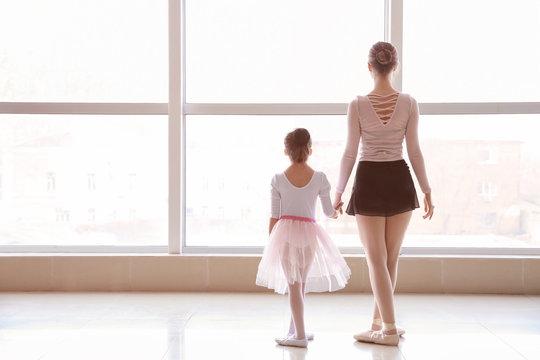 Little ballerina training with coach in dance studio