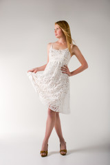 Young girls like a model in a short white dress