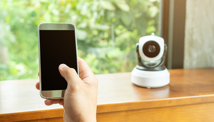 Smartphone connecting with security IP camera on a wooden table.
