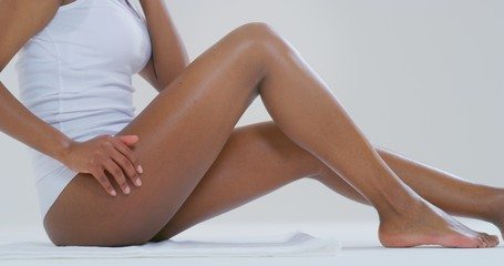 Close up of young dark skin woman with perfect body touching gently her hairless soft and silky legs after depilation isolated on a white background.