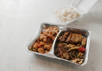 Asian fast food from delivery service in a foil container and rice in a foam box on a bright background, high angle view from above, copy space