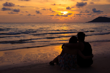 young couple sitting on beach with sunset