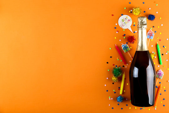 Bottle of champagne without label, streamers, candles and other party attributes on bright orange paper background. Speech bubble with Happy Birthday text. Close up, copy space, top view, flat lay.