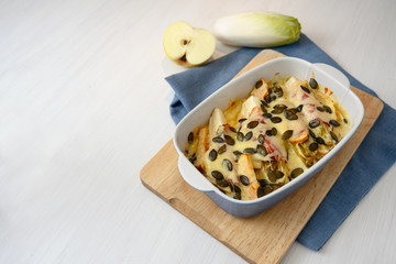 gratin from endives or chicory with apple, ham, cheese and pumpkin seeds in a baking casserole on kitchen board and a blue napkin, white table with copy space