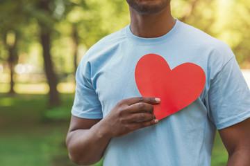 Fototapeta Black man holding red heart on his chest obraz