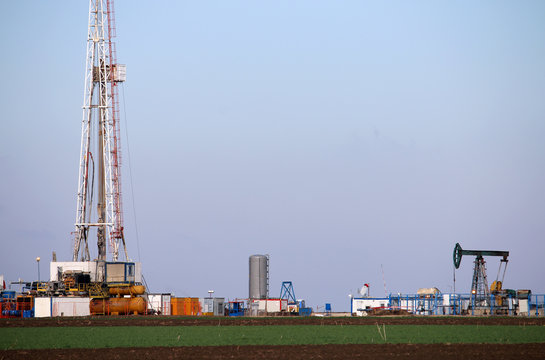 Oil and gas drilling rig and pump jack in oilfield mining industry
